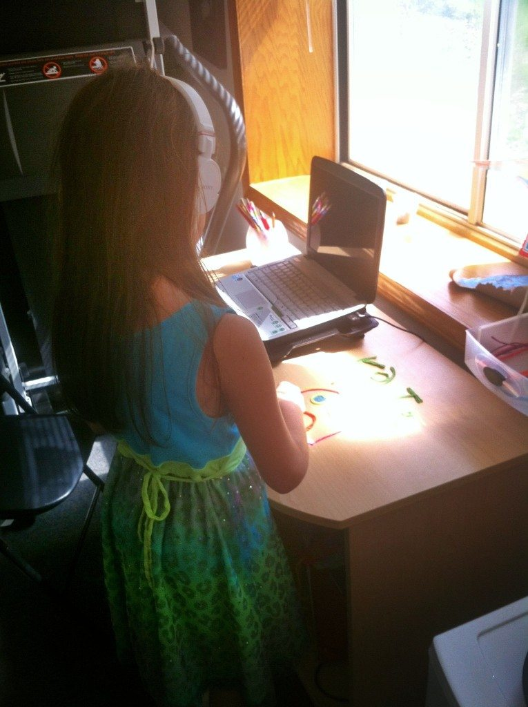 LittleMissSunshine standing up and using some manipulatives while she listens to her lesson for the day